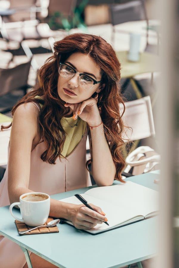 femme d'affaires songeuse dans des lunettes se reposant à la table avec le carnet et la tasse de café photos stock