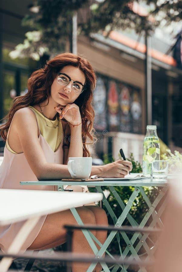 femme d'affaires songeuse dans des lunettes se reposant à la table avec le carnet et la tasse de café photographie stock libre de droits