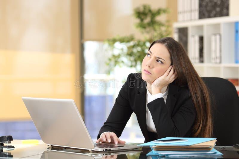 Femme d'affaires songeuse inquiétée au bureau photos stock