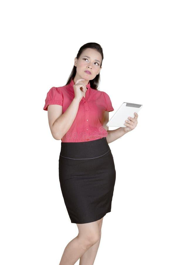Femme d'affaires songeuse travaillant avec un comprimé sur le studio photo libre de droits
