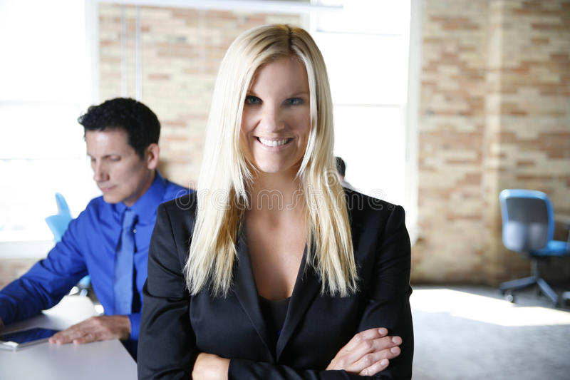 Femme d'affaires souriant avec l'homme d'affaires travaillant dans le bureau moderne de brique urbaine photographie stock libre de droits