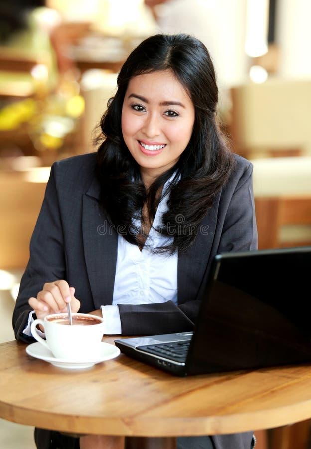 Femme d'affaires souriant tout en remuant un café image stock