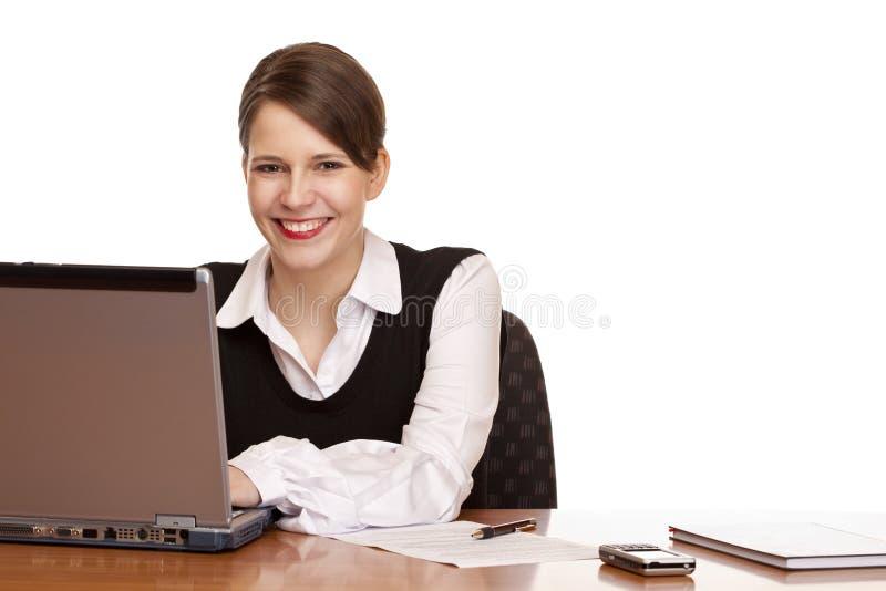 Femme d'affaires sur des travaux de bureau sur l'ordinateur portatif images stock