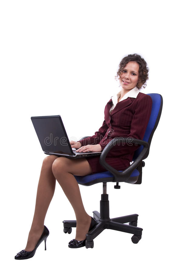 Femme d'affaires sur la présidence de bureau utilisant l'ordinateur portatif images stock