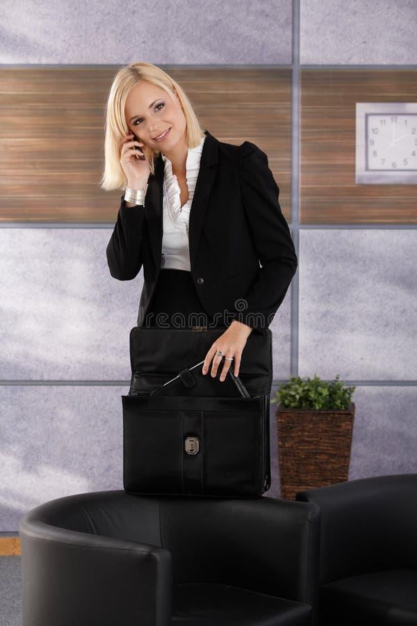 Femme d'affaires sur la serviette d'ouverture de téléphone photo libre de droits