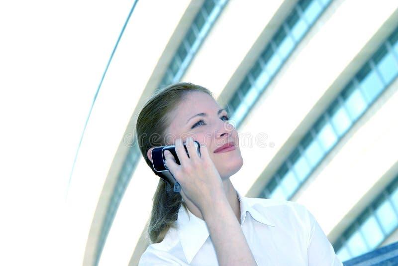 Femme d'affaires sur la teinte de bleu de téléphone portable images stock