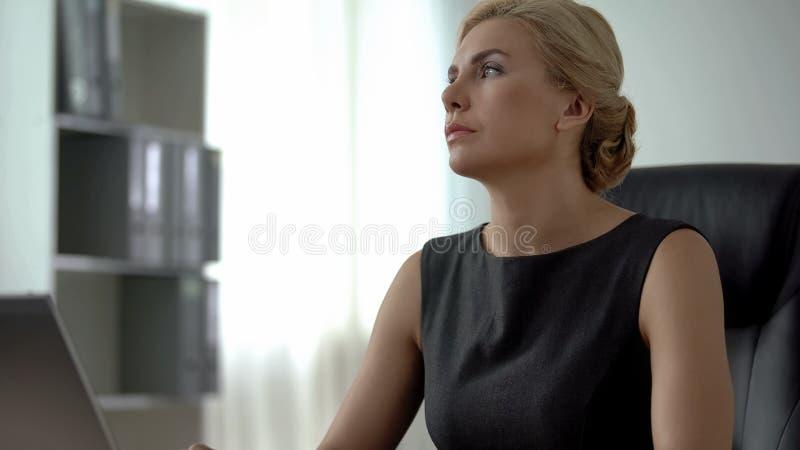 Femme d'affaires surchargée s'asseyant au bureau, heures de travail irrégulières, effort photos libres de droits