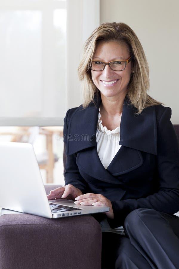 Femme d'affaires télétravaillant à la maison Sur un ordinateur portable Sourire photos stock