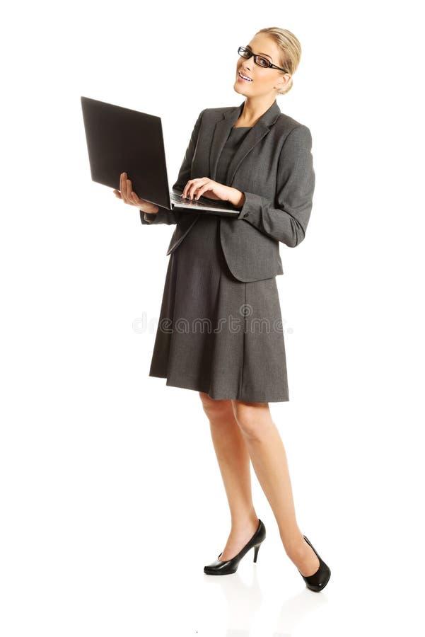 Femme d'affaires tenant et tenant un ordinateur portable images libres de droits