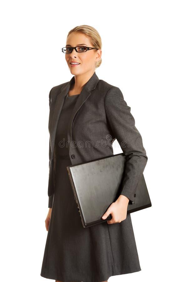 Femme d'affaires tenant et tenant un ordinateur portable image libre de droits