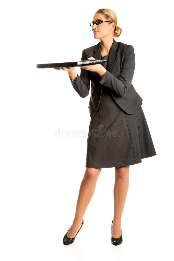 Femme d'affaires tenant et tenant un ordinateur portable photographie stock