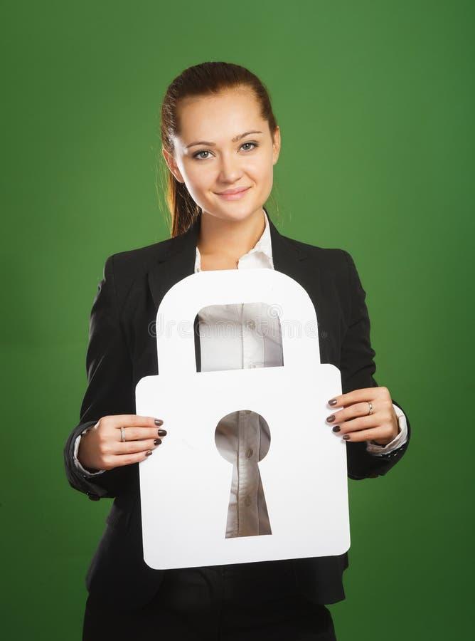 Femme d'affaires tenant la serrure de papier sur le fond vert image stock
