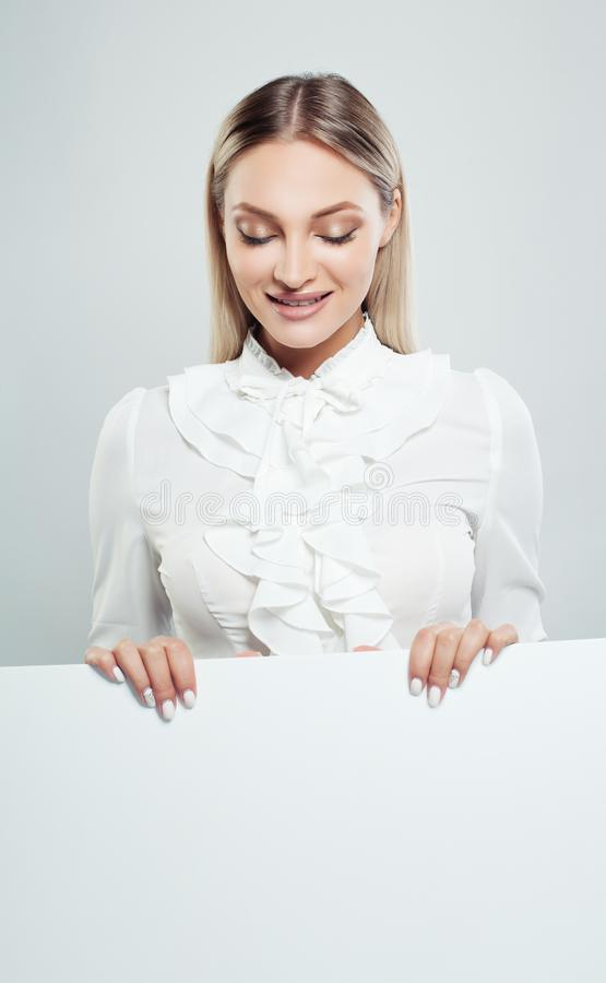 Femme d'affaires tenant le fond vide blanc de bannière de conseil photo stock