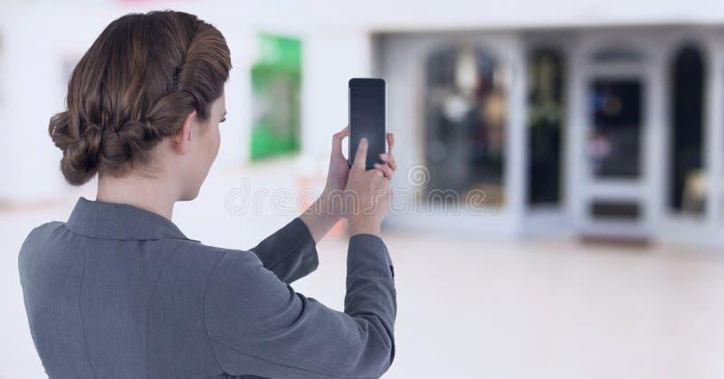 Femme d'affaires tenant le téléphone portable dans le centre commercial images stock