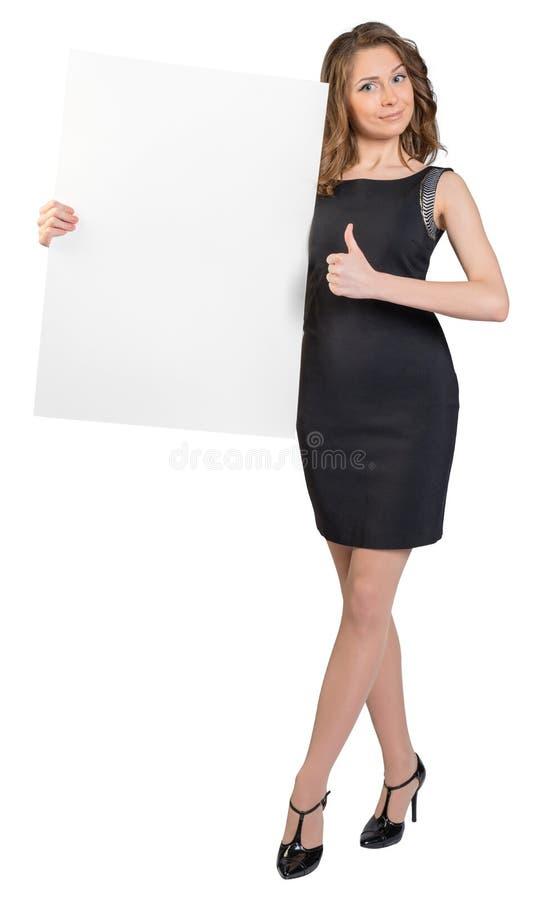 Femme d'affaires tenant un grand panneau d'affichage vide et photo libre de droits