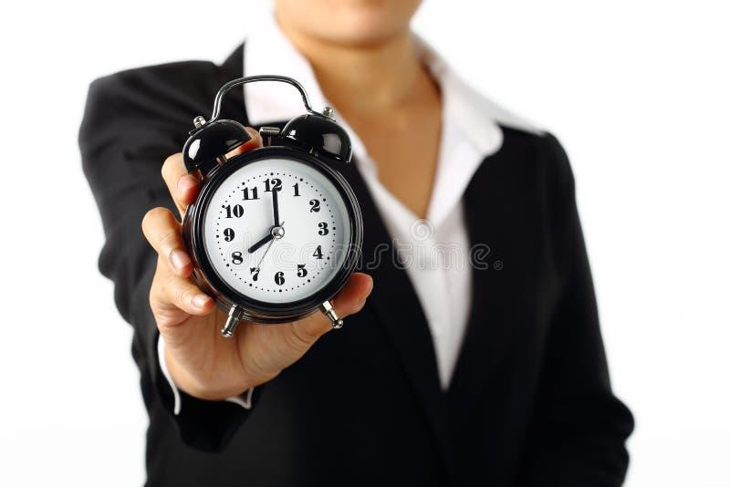 Femme d'affaires tenant une alarme de minuterie image stock