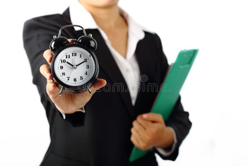 Femme d'affaires tenant une alarme 10 de minuterie 10h du matin d'isolement sur le blanc photographie stock