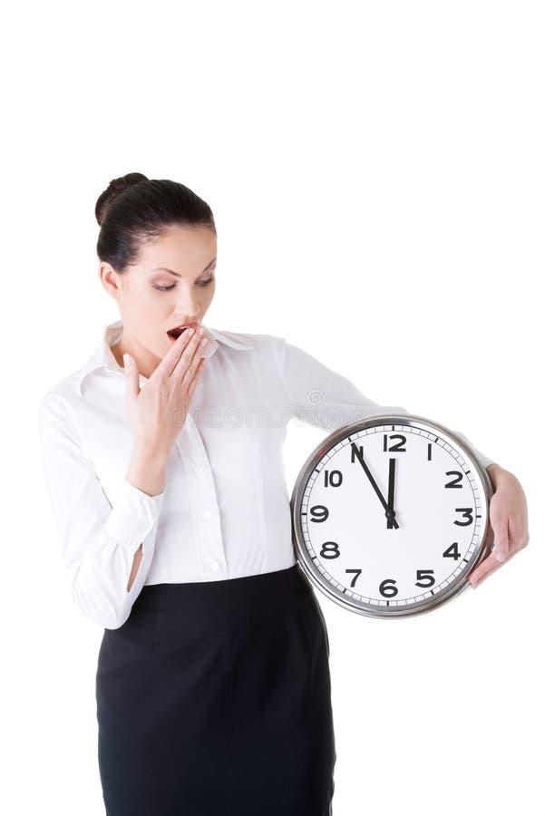 Femme d'affaires tenant une horloge et baîllant. photos libres de droits