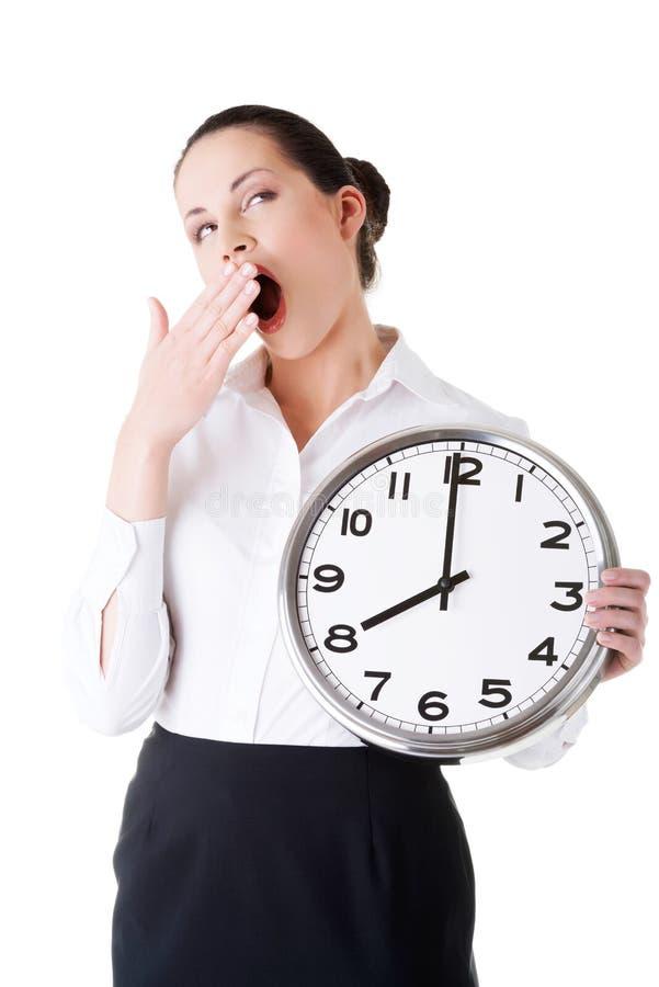 Femme d'affaires tenant une horloge et baîllant. image libre de droits