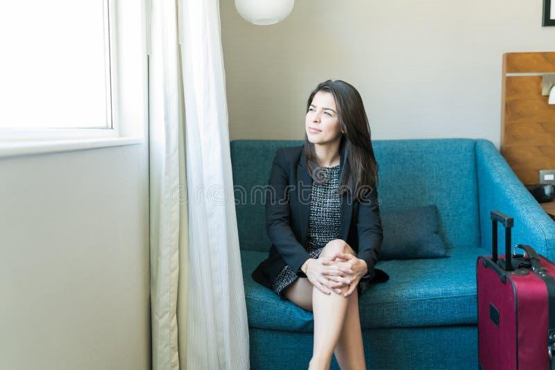 Femme d'affaires Thinking While Looking par la fenêtre dans la chambre d'hôtel images libres de droits
