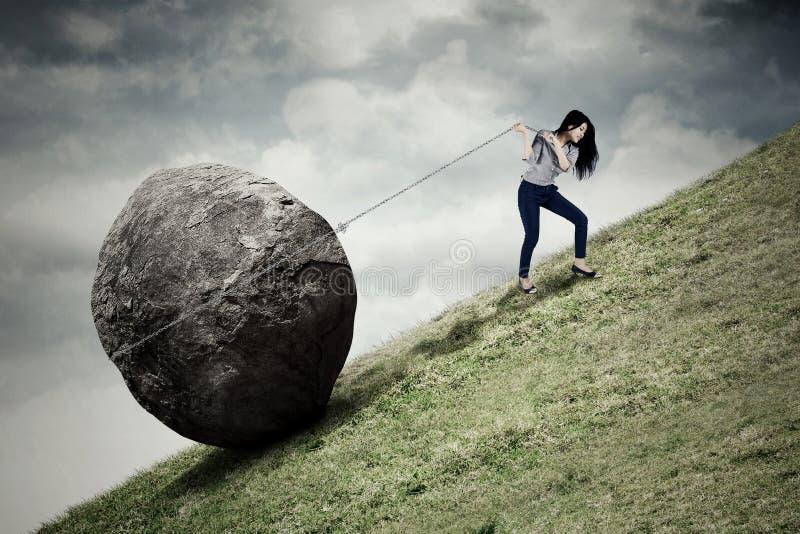 Femme d'affaires tirant la pierre sur la colline photographie stock