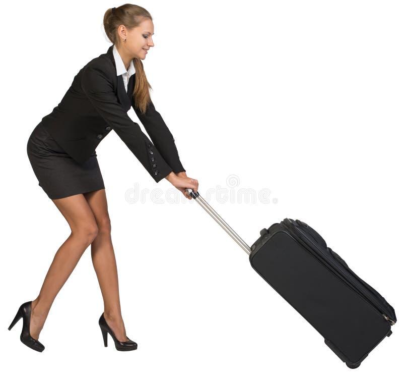 Femme d'affaires traînant la valise à roues lourde à images libres de droits