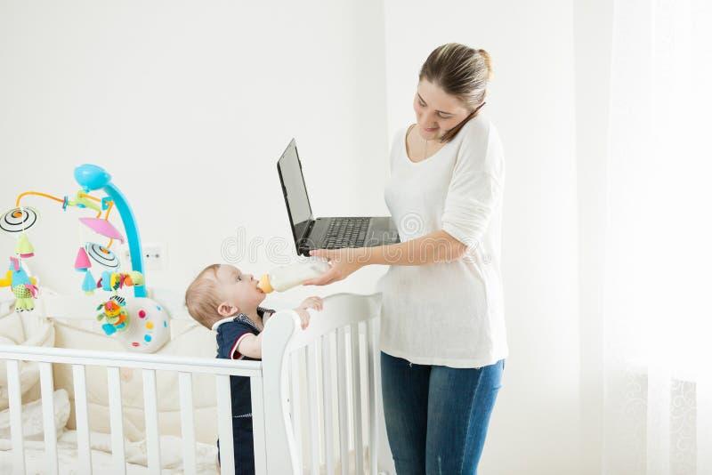 Femme d'affaires travaillant à la maison et donnant le lait à son bébé photo stock