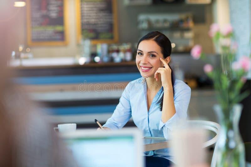 Femme d'affaires travaillant au café image stock