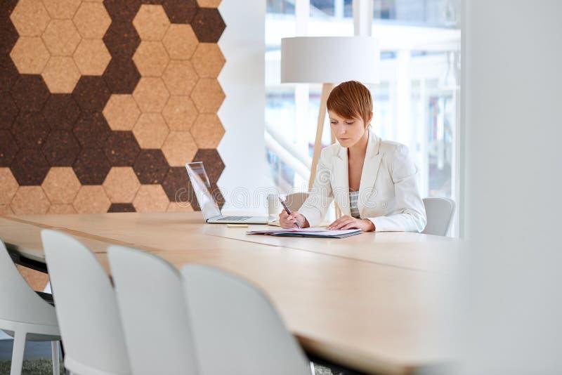 Femme d'affaires travaillant aux écritures dans la salle de réunion moderne de bureau photographie stock libre de droits