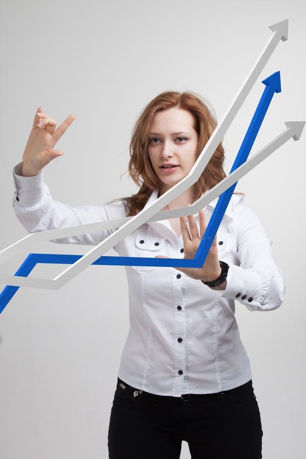Femme d'affaires travaillant avec le graphique de croissance sur le fond gris photos libres de droits