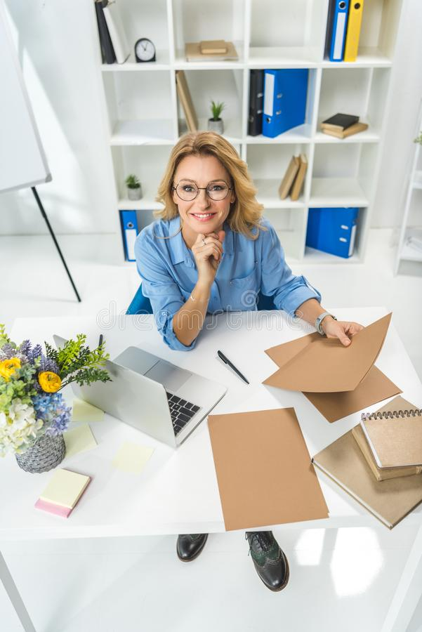 Femme d'affaires travaillant avec les documents et l'ordinateur portable photo stock