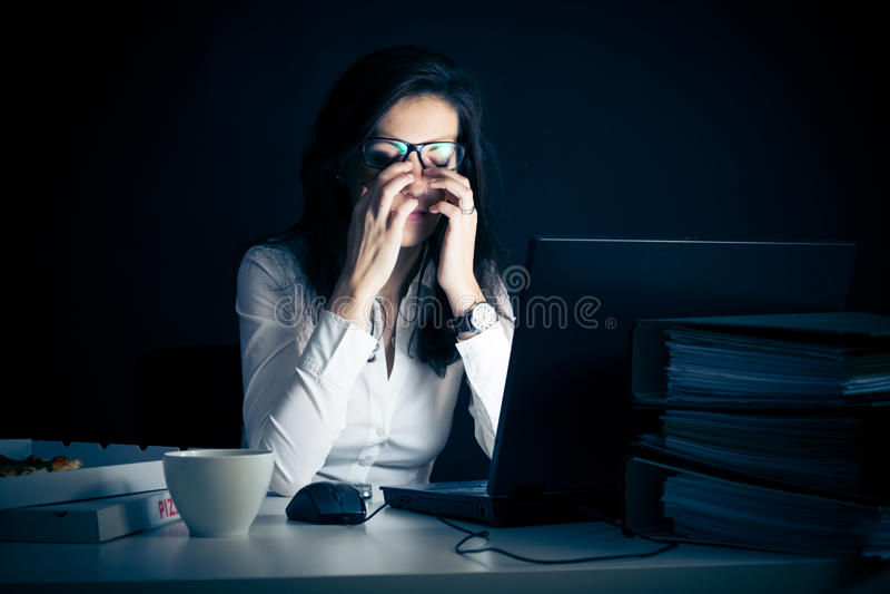 Femme d'affaires travaillant tard image stock