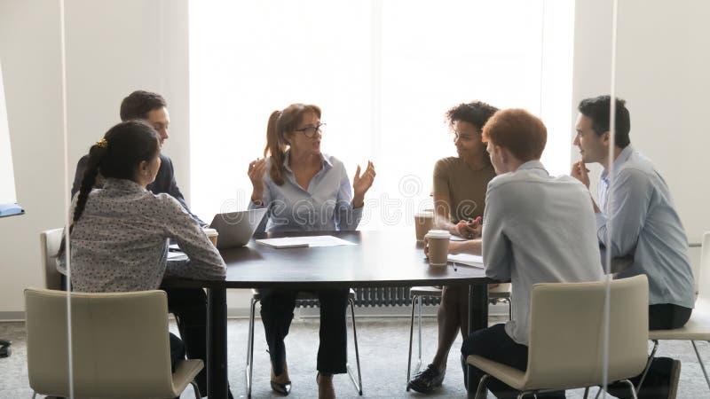 Femme d'affaires d'une cinquantaine d'années parlant aux négociations diverses de groupe à la table de conférence photos stock