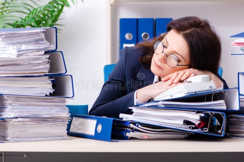 Femme d'affaires d'une cinquantaine d'années peu satisfaite du travail excessif images stock