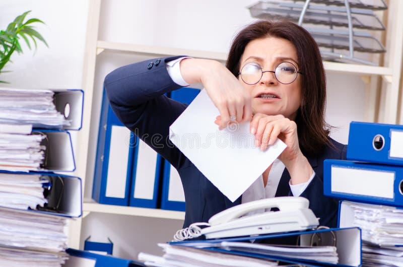 Femme d'affaires d'une cinquantaine d'années peu satisfaite du travail excessif photo libre de droits