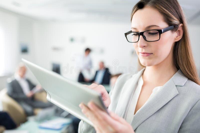 Femme d'affaires Using Digital Tablet dans le bureau photo libre de droits
