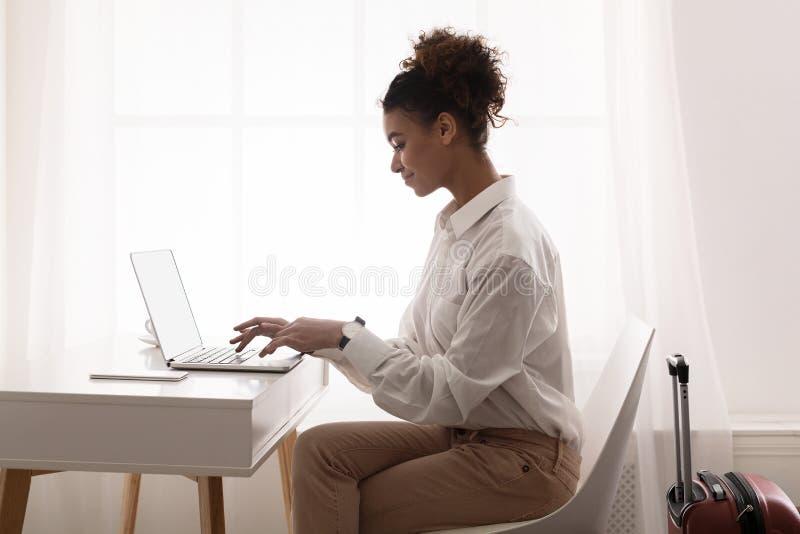 Femme d'affaires Using Laptop, se préparant au voyage d'affaires images stock