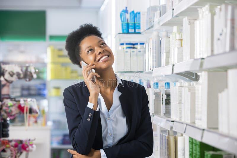 Femme d'affaires Using Mobile Phone dans la pharmacie photos libres de droits