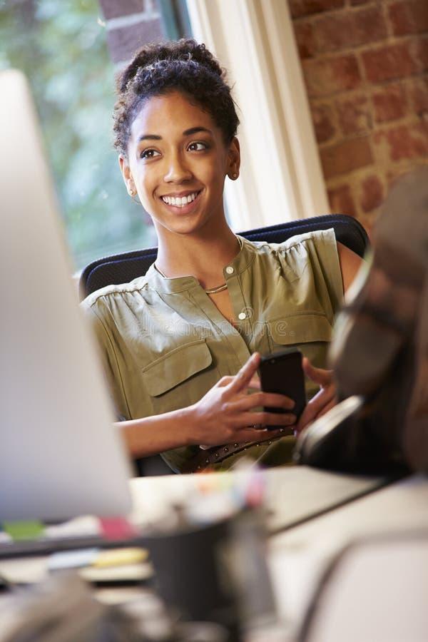 Femme d'affaires Using Mobile Phone dans le bureau créatif photo stock