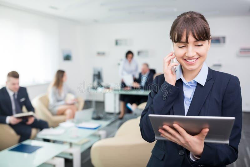 Femme d'affaires Using Mobile Phone et Tablette de Digital dans le bureau photo libre de droits