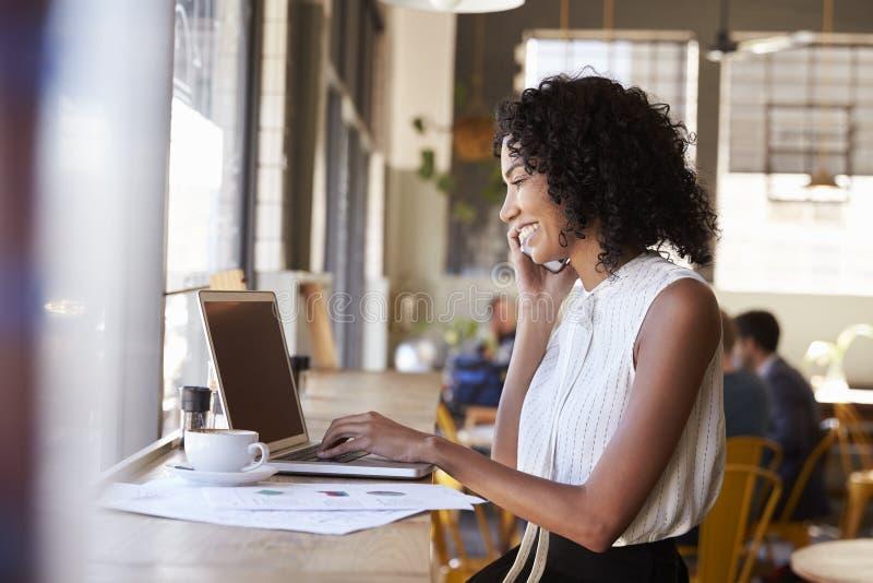 Femme d'affaires Using Phone Whilst travaillant dans le café images libres de droits
