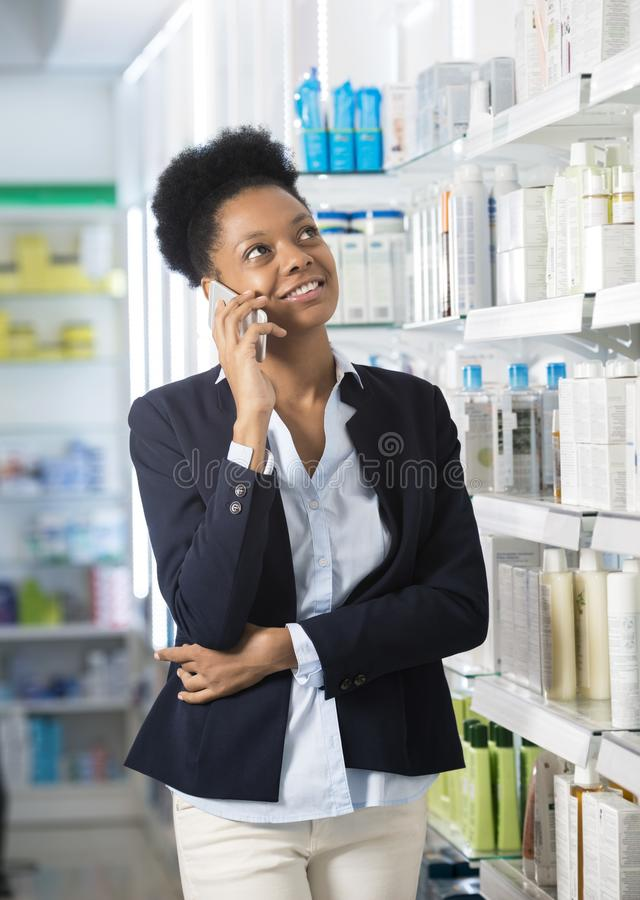 Femme d'affaires Using Smart Phone dans la pharmacie photos stock