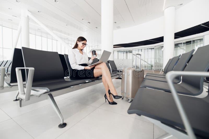 Femme d'affaires utilisant l'ordinateur portable ? l'a?roport se reposant ? la fen?tre image libre de droits