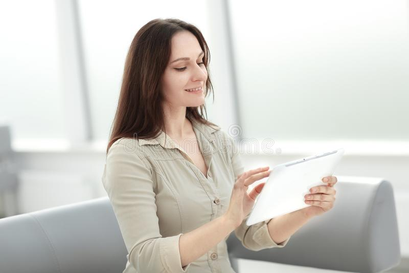 Femme d'affaires utilisant le comprimé numérique se reposant sur le sofa dans le lobby de bureau photographie stock libre de droits