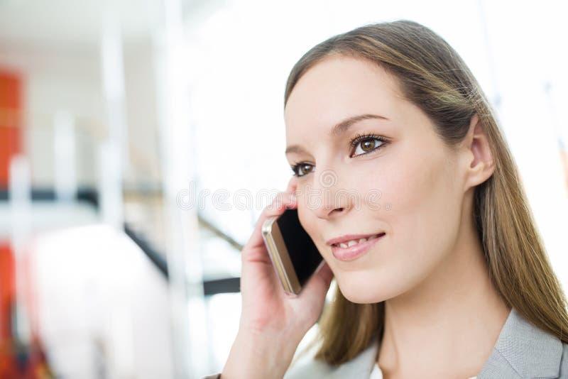 Femme d'affaires utilisant le smartphone dans le bureau images libres de droits