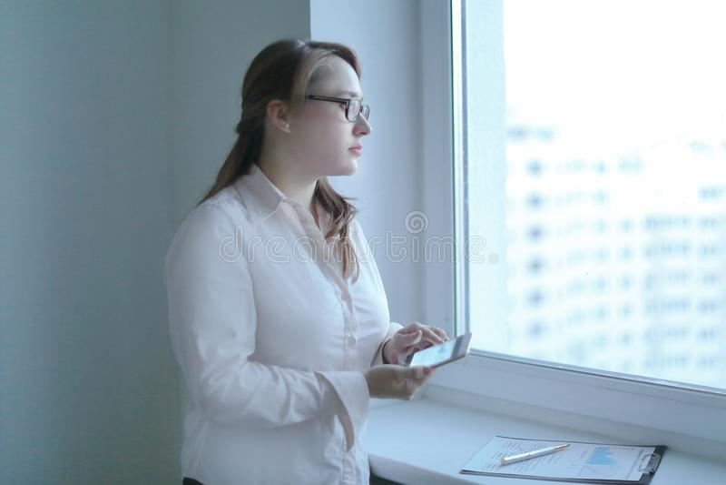 Femme d'affaires utilisant un smartphone tout en se tenant près d'une fenêtre de bureau photo stock