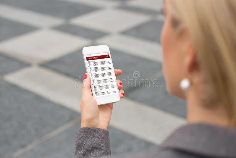 Femme d'affaires vérifiant l'email sur le smartphone photographie stock