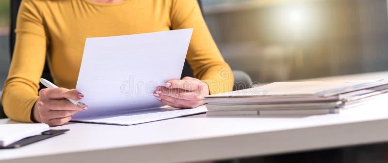 Femme d'affaires vérifiant le document image libre de droits