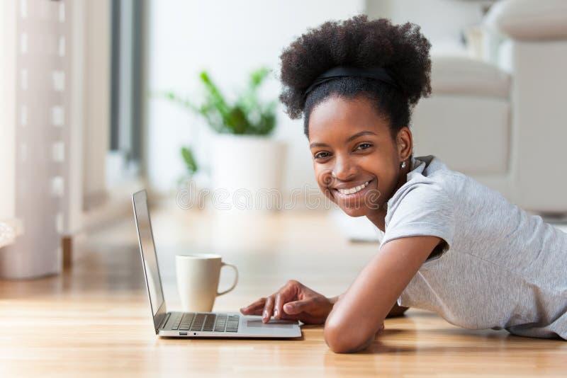 Femme d'afro-américain à l'aide d'un ordinateur portable dans son salon - noir photographie stock