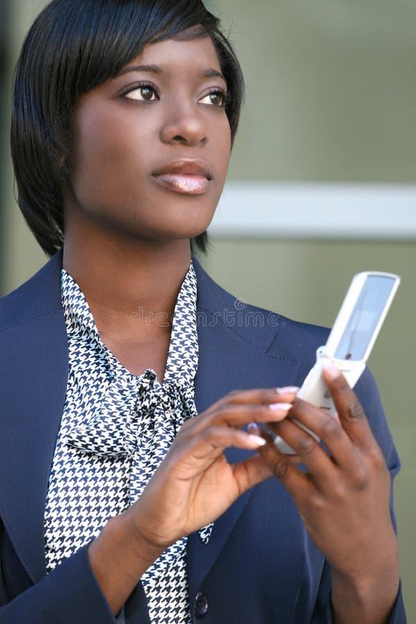 Femme d'Afro-américain à l'extérieur sur le téléphone portable photographie stock libre de droits